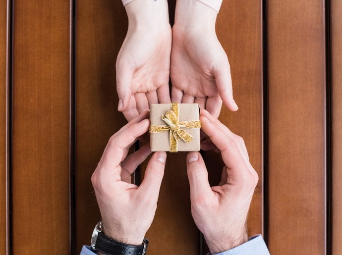 A man handing over a gift box to his partner.