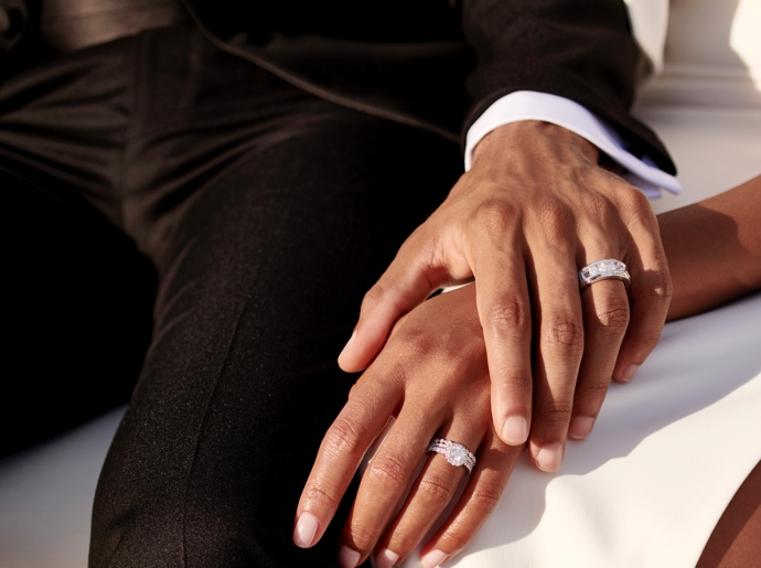 A man holding his wife's hand while wearing wedding bands.