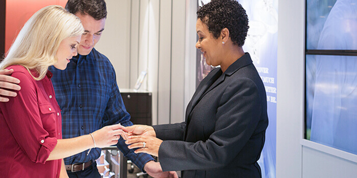 A couple receiving help customizing an engagement ring from an in-store KAY expert