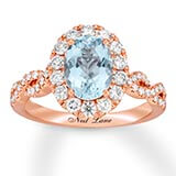 A 14k rose gold band with diamonds and an aquamarine center stone