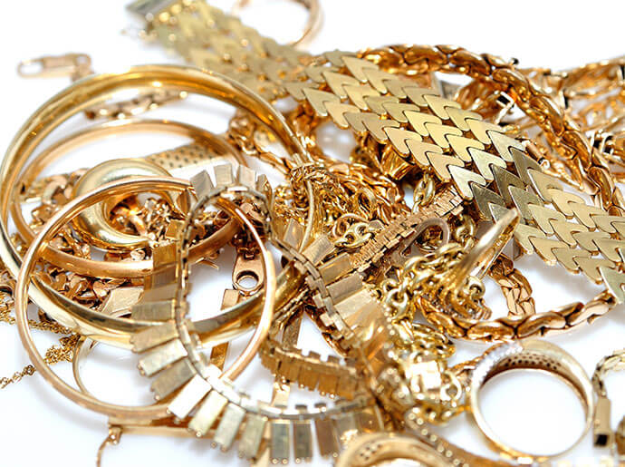 A pile of gold jewelry rests on a white background.
