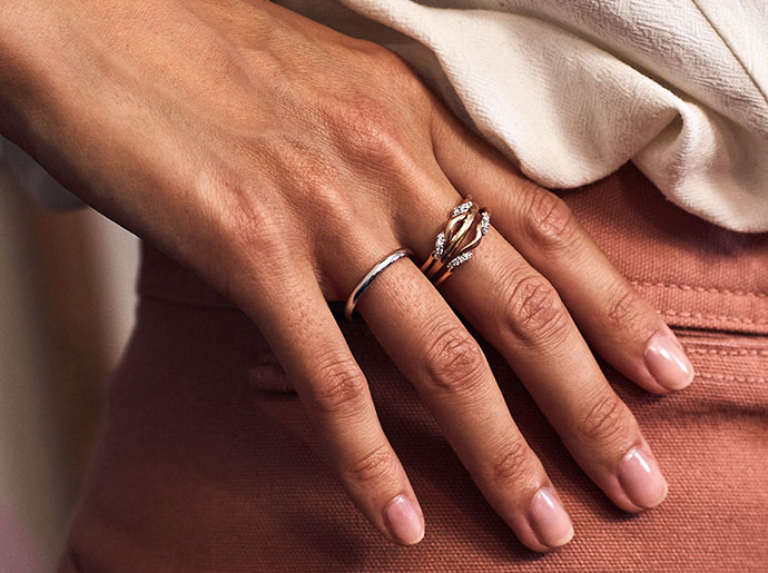 A woman's hand displays gold rings while it rests on her hip.