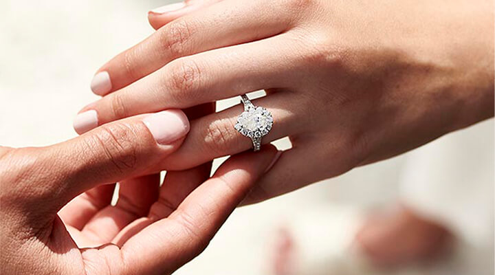 A man placing a diamond engagement ring with a pear-shaped center stone on a woman's hand