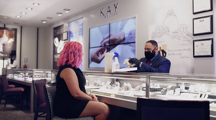 A KAY expert with a mask working with a customer one-on-one and sanitizing jewelry before presenting it for viewing and handling