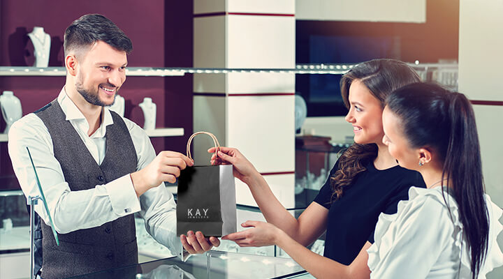 Two women picking up a purchase from a KAY store