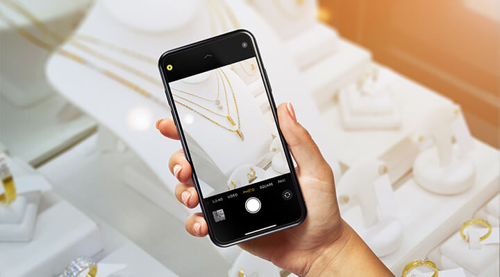 A woman taking a photo of different gold chains with her smartphone