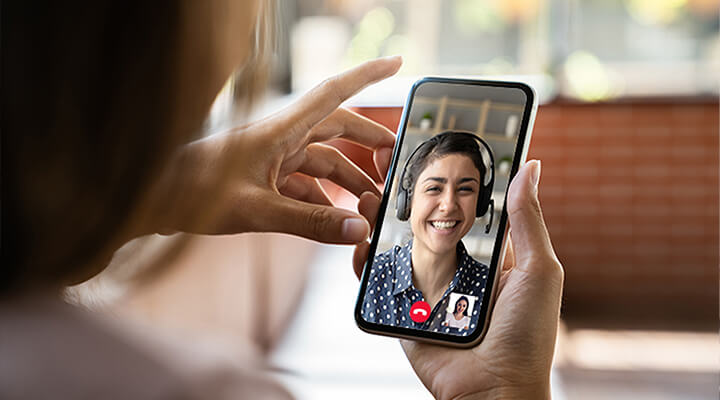 A woman engaged in a virtual consultation with a Jewelry Consultant on her smartphone