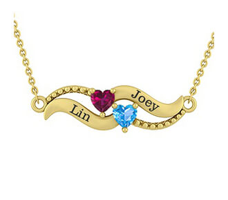 A KAY personalized yellow gold necklace showing the names Lin and Joey with heart-shaped ruby and blue topaz gemstones