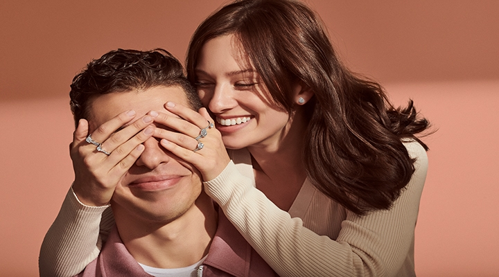 A woman covers her husbands eyes with hands decked out in Modern Creation diamond rings
