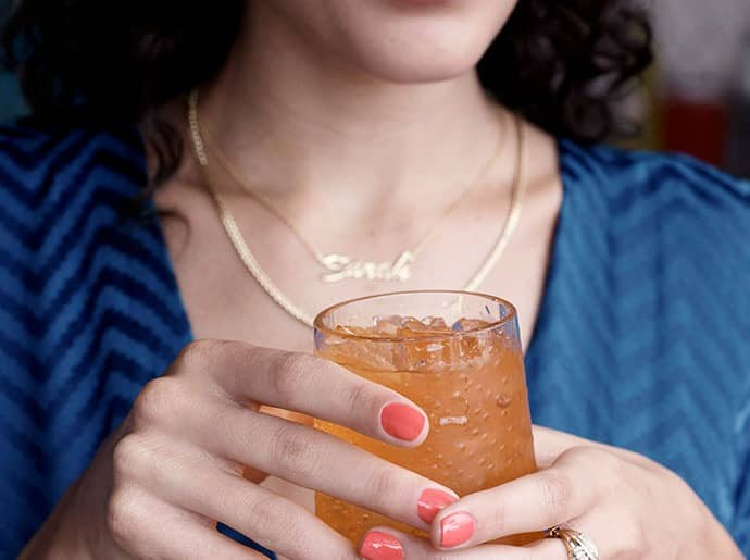 A woman wears a personalized KAY Jewelers necklace.